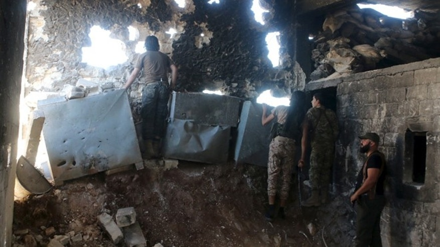 APRIL 19: Harakat Nour al-Din al-Zenki fighters look out inside a damaged building in Handarat area, north of Aleppo Syria April 19, 2016.