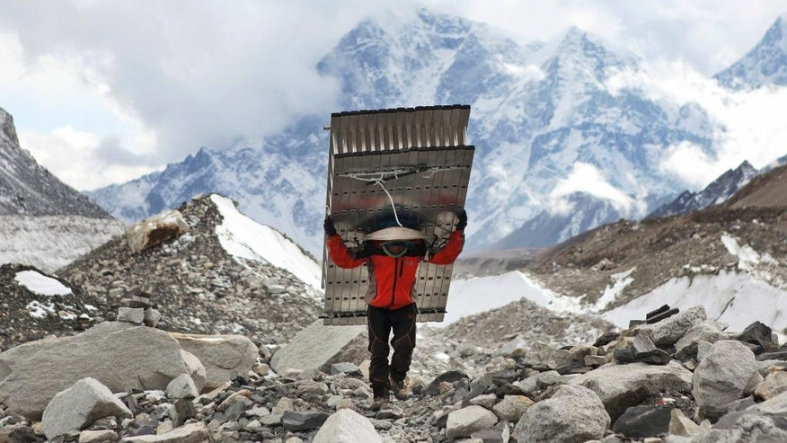 In this March 7, 2016 photo, a porter fetches the ladders for the icefall doctors who will be fixing the route for the climbers trying to attempt the summit of Mt Everest this year at Everest Base Camp in Nepal. The April 2014 avalanche, which killed 13 Sherpa guides and three other Nepali workers, was an immense blow to the Sherpa community. Nearly all the surviving Sherpas refused to continue working that year, demanding, among other things, better working conditions, more insurance, and free education for the children of those killed. Over the past two years the government has enacted a series of policy changes, from stationing officials at Base Camp to creating a welfare fund for the families of the Sherpa dead, in large part to convince climbers and trekkers to keep coming back to Everest. (AP Photo/Tashi Sherpa)