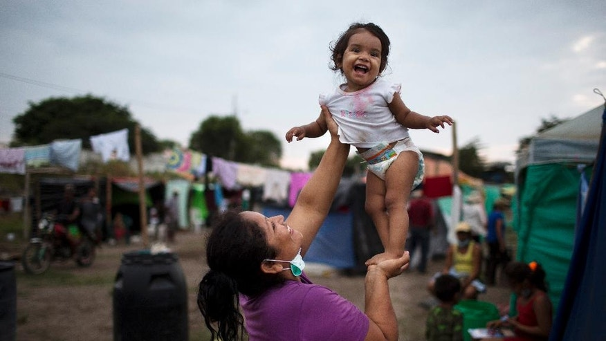 Patricia Sambrano plays with her granddaughter Ailin at a makeshift camp organized by families who lost their homes to the 7.8-magnitude earthquake, in Canoas, Ecuador, Thursday, April 21, 2016. President Rafael Correa said Ecuador's worst earthquake in decades caused billions of dollars of damage and he is raising sales taxes and putting a one-time levy on millionaires to help pay for reconstruction. (AP Photo/Rodrigo Abd)