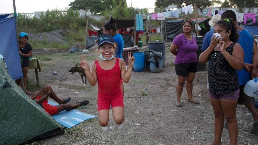 Karen Farias, in red, plays with friends at a makeshift camp organized by families who lost their homes to the earthquake, in Canoas, Ecuador, Thursday, April 21, 2016. President Rafael Correa said Ecuador's worst earthquake in decades caused billions of dollars of damage and he is raising sales taxes and putting a one-time levy on millionaires to help pay for reconstruction. (AP Photo/Rodrigo Abd)