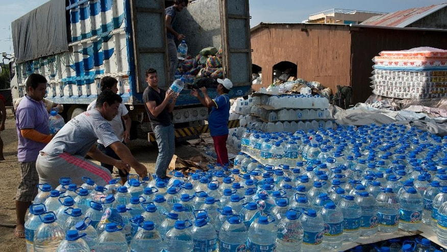 Volunteers download bottled water at a makeshift storage facility in Canoas, Ecuador, Thursday, April 21, 2016. President Rafael Correa said Ecuador's worst earthquake in decades caused billions of dollars of damage and he is raising sales taxes and putting a one-time levy on millionaires to help pay for reconstruction. (AP Photo/Rodrigo Abd)