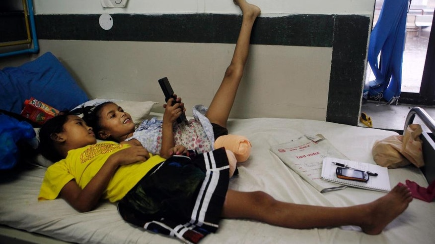 In this July 6, 2015, photo, Nepalese amputee victims and best of friends, Khendo Tamang, left, and Nirmala Pariyar, both 8, play on a mobile phone at the Bir Trauma Center in Kathmandu, Nepal. Each girl lost one leg in Nepal's massive April 25, 2015 earthquake that killed nearly 9,000 people dead and more than 22,000 injured. (AP Photo/Niranjan Shrestha)