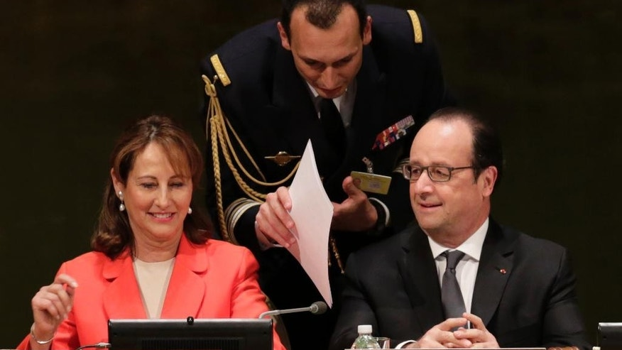 Francois Hollande, right, President of France, is handed papers prior to the signing ceremony for the Paris Agreement on climate change, Friday, April 22, 2016 at U.N. headquarters. (AP Photo/Mark Lennihan)