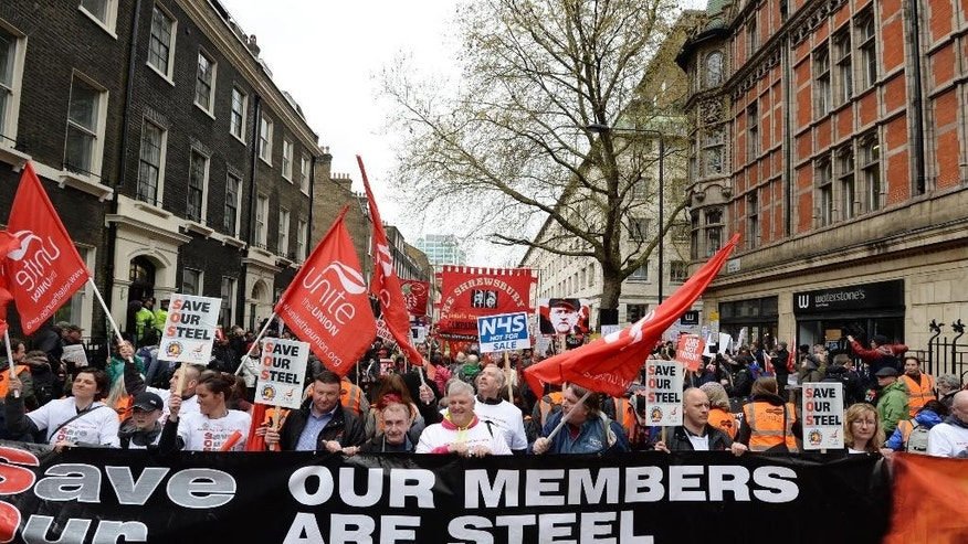 This Saturday, April 16, 2016, photo shows campaigners marching in an anti-austerity demonstration in central London. Tata Steel, a company based in India, announced plans to sell its U.K. businesses, which were losing 1 million pounds ($1.4 million) a day amid high costs and a glut of cheap Chinese steel in global markets. That raised fears the plant would close if Tata couldn't find a buyer, eliminating 4,000 jobs and severing the economic lifeline of the town of Port Talbot. (Stefan Rousseau/PA via AP)  UNITED KINGDOM OUT; NO SALES; NO ARCHIVES; MANDATORY CREDIT