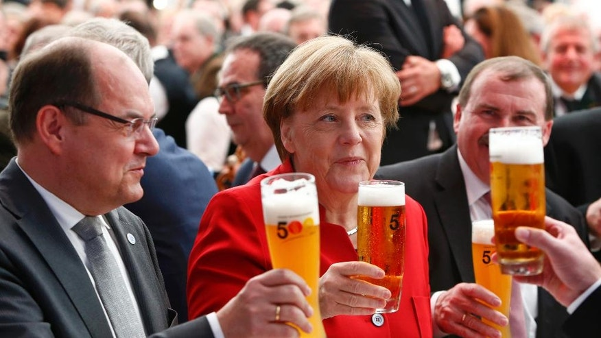 German Chancellor Angela Merkel, center attends the 500th anniversary ceremony of the German Beer Purity Law in Ingolstadt, Germany, Friday, April 22, 2016. (Michaela Rehle/Pool Photo via AP)
