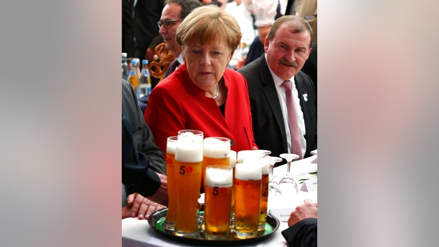 German Chancellor Angela Merkel, left, attends the 500th anniversary ceremony of the German Beer Purity Law in Ingolstadt, Germany, Friday, April 22, 2016. (Michaela Rehle/Pool Photo via AP)