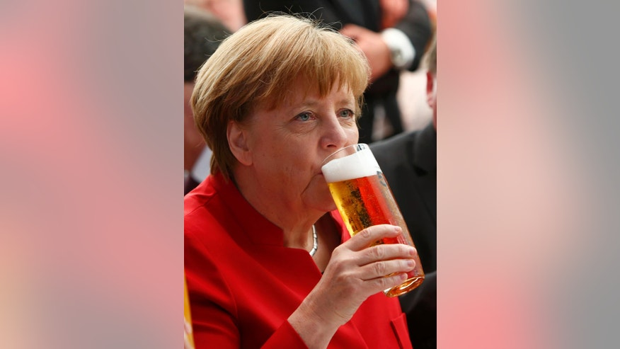 German Chancellor Angela Merkel drinks beer during the 500th anniversary ceremony of the German Beer Purity Law in Ingolstadt, Germany, Friday, April 22, 2016. (Michaela Rehle/Pool Photo via AP)