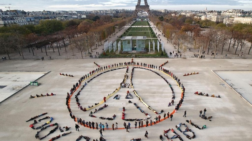 "FILE - In this Dec. 6, 2015 file photo, environmentalist activists form a human chain representing the peace sign and the spelling out ""100% renewable"", on the side line of the COP21, United Nations Climate Change Conference near the Eiffel Tower in Paris. Four months after negotiating a global climate agreement in Paris, government officials are coming to New York on Friday, April 22, 2016, to sign the pact in a ceremony at the United Nations. (AP PhotoMichel Euler, File)"