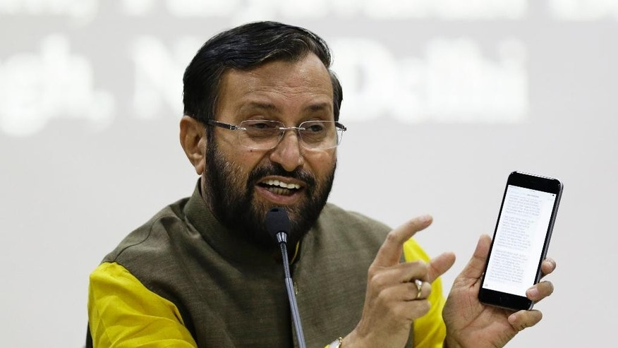 FILE - In this April 19, 2016 file photo, Indian Environment Minister, Prakash Javadekar, shows how messages are automatically sent to his mobile device when pollution at certain effluent treatment places remain higher than a stipulated measure for over 15 minutes, at a press conference in New Delhi, India. Javadekar enumerated several measures taken by India to meet its goals to combat climate change after the Paris agreement. Four months after negotiating a global climate agreement in Paris, government officials are coming to New York on Friday, April 22, 2016, to sign the pact in a ceremony at the United Nations. (AP Photo/Saurabh Das, File)