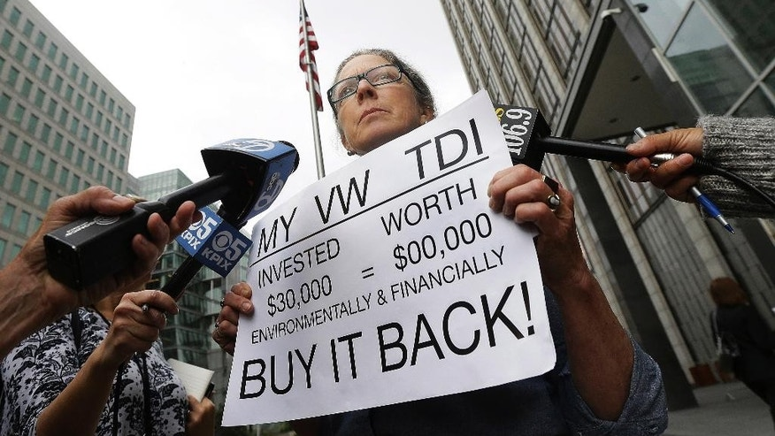 Joyce Ertel Hulbert, owner of a 2015 Volkswagen Golf TDI, holds a sign while interviewed outside of the Phillip Burton Federal Building in San Francisco, Thursday, April 21, 2016. An agreement will give consumers who bought nearly 600,000 Volkswagen vehicles rigged to cheat on emissions tests the option of having the automaker buy back the cars or fix them, a judge said Thursday. (AP Photo/Jeff Chiu)