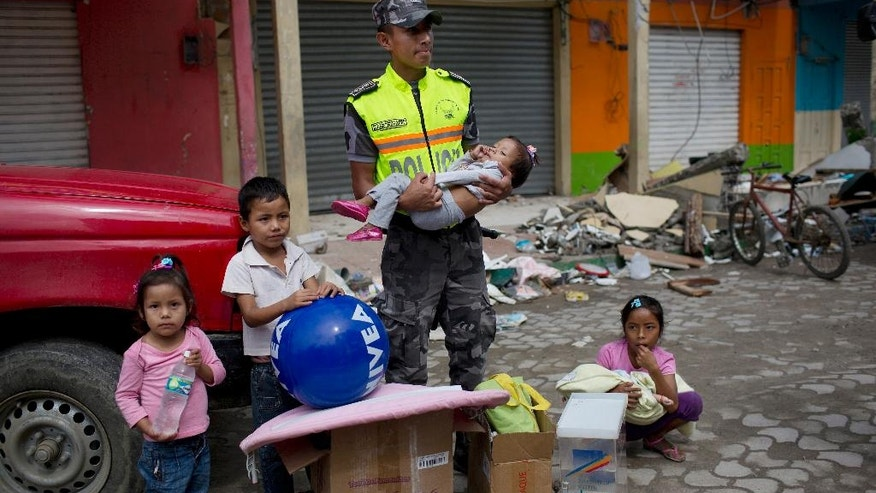Police cadet Erick Palacios holds one-year-old Juanita Yamile Marquez as he watches over her and her siblings while their mother searches for usable items inside an earthquake-damaged building, with permission from the owners, on the outskirts of Pedernales, Ecuador, Saturday, April 23, 2016. The earthquake damage has added to the already heavy economic hardships being felt in this OPEC nation because of a collapse in world oil prices. (AP Photo/Rodrigo Abd)