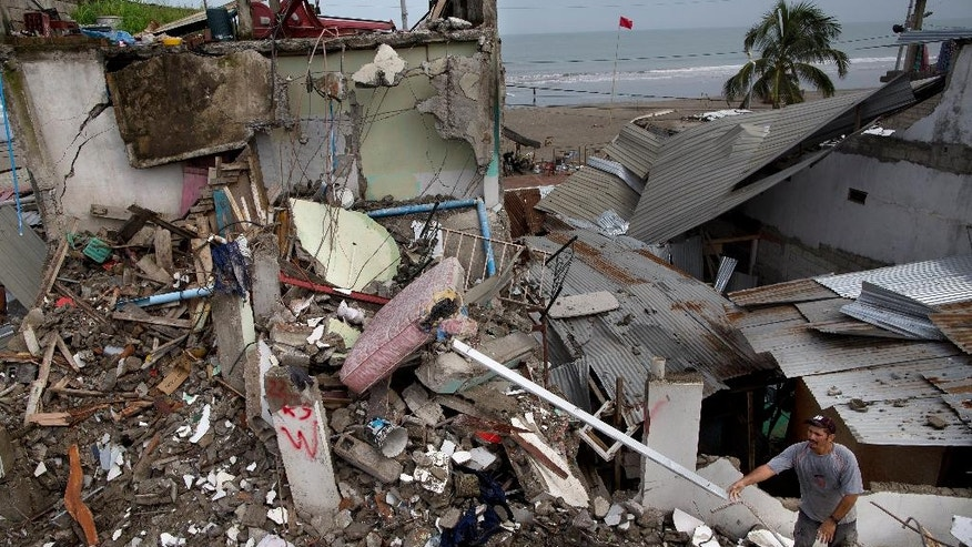 A man collects metal to recycle before a bulldozer demolishes homes, one week after a devastating earthquake in Pedernales, Ecuador, Saturday, April 23, 2016. Ecuadorean officials say the number of people left homeless climbed to over 25,000. (AP Photo/Rodrigo Abd)