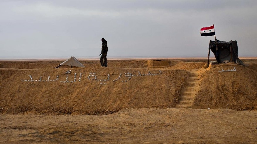 "In this Thursday, April 14, 2016 photo, a Syrian soldier walks on a sand barrier with Arabic that reads ""Syria al-Assad,"" in Palmyra, in the central city of Homs, Syria. Looking out from the Syrian capital these days, one can understand why President Bashar Assad would be in no hurry to make compromises at peace talks in Geneva, let alone consider stepping down as the opposition demands. (AP Photo/Hassan Ammar)"