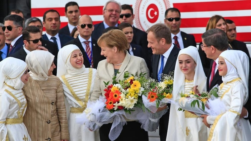 German Chancellor Angela Merkel, centre, accompanied by EU Council President Donald Tusk, right, talks to young women during a visit to the Nizip refugee camp in Gaziantep province, southeastern Turkey, Saturday, April 23, 2016. Merkel and the top European Union officials, under pressure to reassess a migrant deportation deal with Turkey, are traveling close to Turkey's border with Syria on Saturday in a bid to bolster the troubled agreement. (AP Photo/Lefteris Pitarakis)