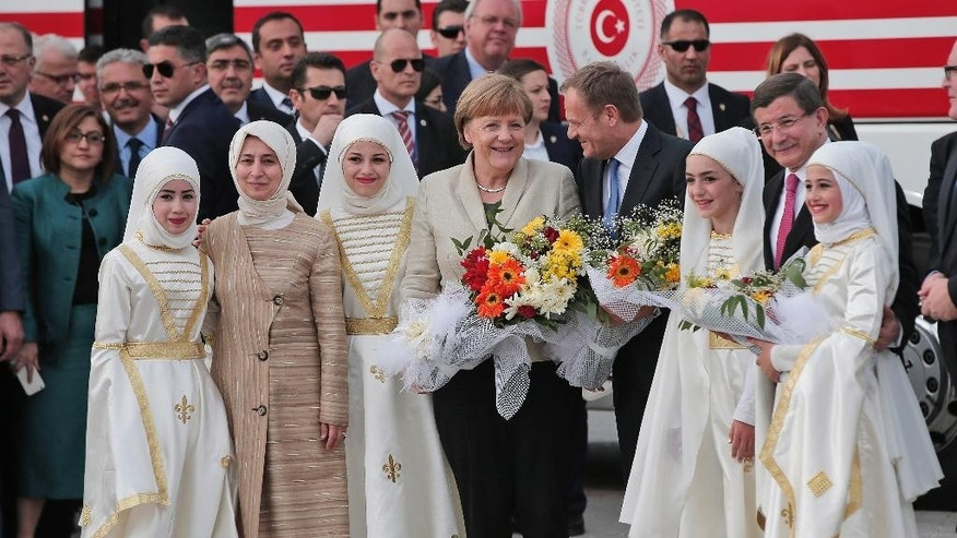German Chancellor Angela Merkel, centre, accompanied by EU Council President Donald Tusk, 2rd right, Turkish Prime Minister Ahmet Davutoglu, right, poses for pictures during a visit at the Nizip refugee camp in Gaziantep province, southeastern Turkey, Saturday, April 23, 2016. Merkel and the top European Union officials, under pressure to reassess a migrant deportation deal with Turkey, are traveling close to Turkey's border with Syria on Saturday in a bid to bolster the troubled agreement. (AP Photo/Lefteris Pitarakis)
