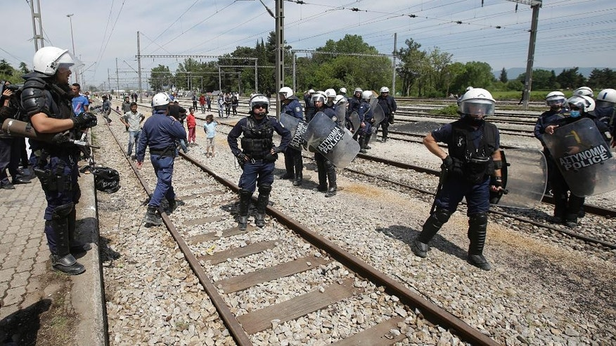 Greek policemen stand on the tracks of a train station turned into a makeshift camp crowded of migrants and refugees at the northern Greek border point of Idomeni, Greece, Friday, April 22, 2016. The European Commission says the number of migrants arriving in Greece from Turkey has slowed dramatically from more than 50,000 in February to around 7,000 over the past 30 days. But Greece, currently home to 54,000 stranded migrants seeking to travel deeper into Europe, faces unrelenting pressure as the long-promised relocation of asylum seekers from Greece to other EU countries moves pitifully slowly. (AP Photo/Gregorio Borgia)