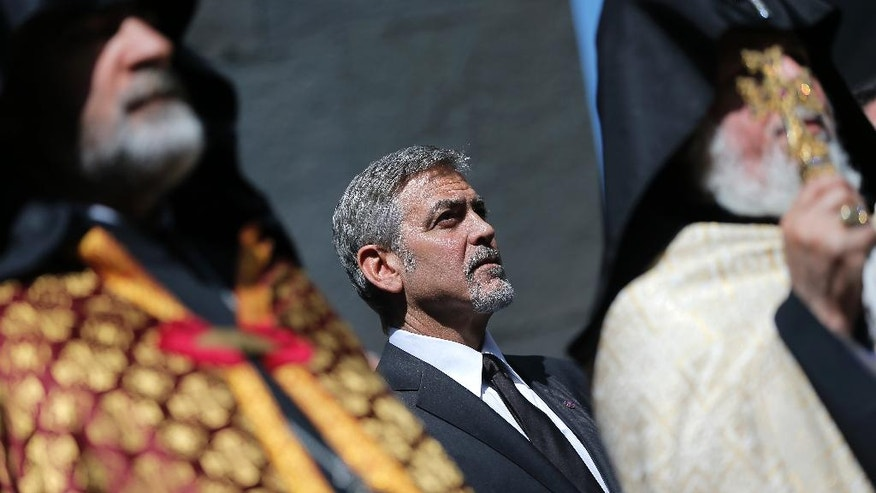 US actor George Clooney, center, attends a ceremony at a memorial for Armenians killed by the Ottoman Turks, in Yerevan, Armenia on Sunday, April 24, 2016. The killing of more than 200 Armenian intellectuals on April 24, 1915 is regarded as the start of the massacre that is widely viewed by historians as genocide. But modern Turkey, the successor to the Ottoman Empire, vehemently rejects the charge. Clooney has been a prominent voice in favor of countries recognizing the killings as genocide, which the United States has not done. (Vahan Stepanyan/ PAN Photo via AP)
