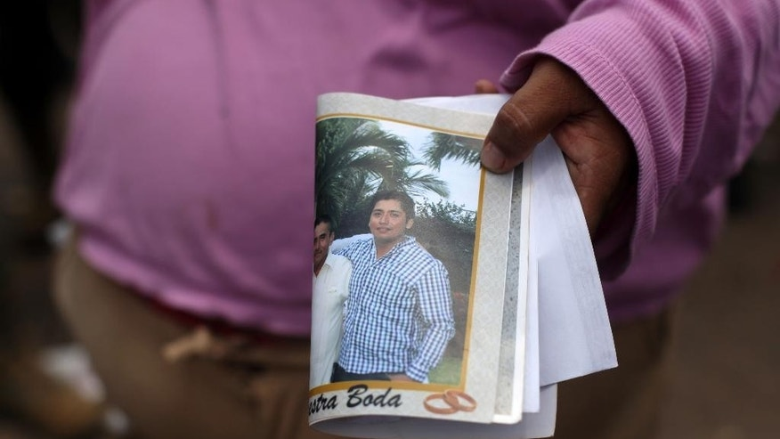 Rosa Villalobos holds holds up a photo of her son, Luis Alfonso Ruiz, as she tries to get information on his whereabouts outside one of the main entrances to the Pajaritos petrochemical complex in the city of Coatzacoalcos, Mexico, Thursday, April,  21, 2016. Ruiz is one of several workers still unaccounted for while at least 13 people are now confirmed dead and scores of others have been injured in an explosion inside this plant. (AP Photo/Felix Marquez)