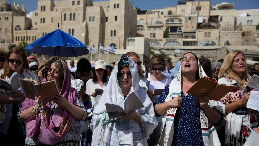 "Jewish women wear prayer shawls as they pray during the Jewish holiday of Passover in front of the Western Wall, the holiest site where Jews can pray, in Jerusalem's Old City, Sunday, April 24, 2016. A liberal women's group has held a special Passover prayer service at a Jerusalem holy site, drawing criticism from the site's ultra-Orthodox rabbi, who called it a ""provocation."" (AP Photo/Ariel Schalit)"