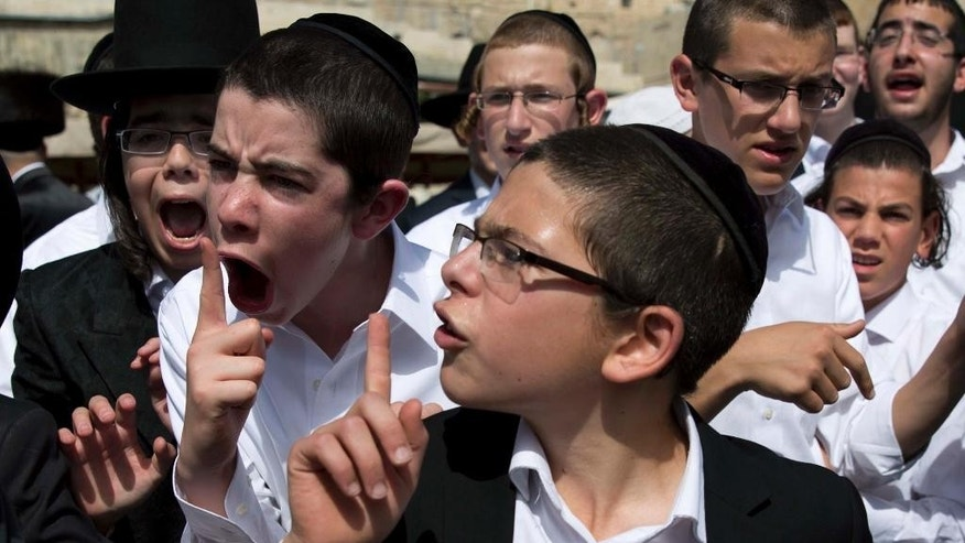 "Ultra-Orthodox Jewish youth yell at a journalist covering the Jewish women's prayer during the Jewish holiday of Passover in front of the Western Wall, the holiest site where Jews can pray, in Jerusalem's Old City, April 24, 2016. A liberal women's group has held a special Passover prayer service at a Jerusalem holy site, drawing criticism from the site's ultra-Orthodox rabbi, who called it a ""provocation."" (AP Photo/Ariel Schalit)"