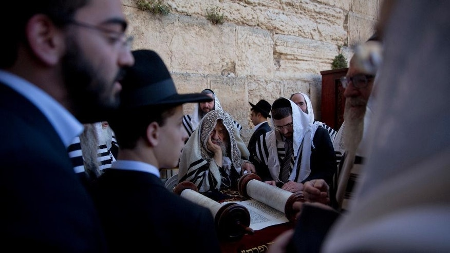 Covered in prayer shawls, ultra-Orthodox Jewish men read from a Thora scroll during the Jewish holiday of Passover in front of the Western Wall, the holiest site where Jews can pray, in Jerusalem's Old City, Sunday, April 24, 2016. (AP Photo/Ariel Schalit)