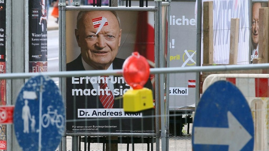 In this photo taken Tuesday, April 19, 2016 a construction site is set up in front of election posters of Andreas Kohl, candidate for presidential elections of Austrian People's Party, OEVP, in Vienna, Austria. For the first time, Austria's next president will likely be someone who is not officially backed by one of the two parties that have dominated government since the end of World War II. That reflects massive voter unhappiness _ and spells possible political turmoil ahead. (AP Photo/Ronald Zak)