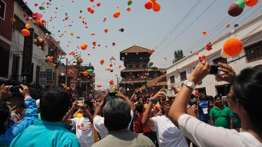 Nepalese people release balloons in memory of those who died in last year's devastating earthquake in Kathmandu, Nepal, Saturday, April 23, 2016. The April 25, 2015, earthquake, killed nearly 9,000 people. (AP Photo/Niranjan Shrestha)
