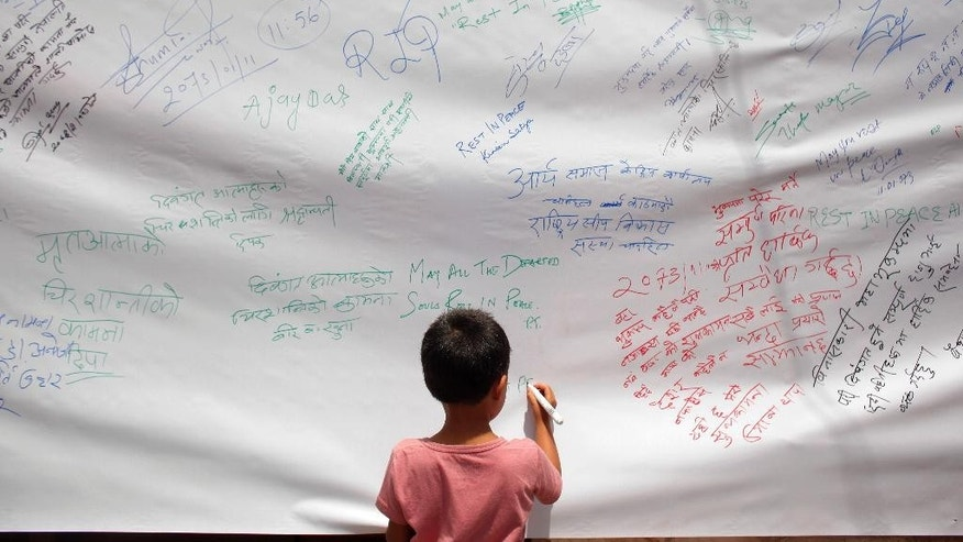 A Nepalese boy writes condolence messages as others release balloons in memory of those who died in last year's devastating earthquake in Kathmandu, Nepal, Saturday, April 23, 2016. The April 25, 2015, earthquake, killed nearly 9,000 people. (AP Photo/Niranjan Shrestha)