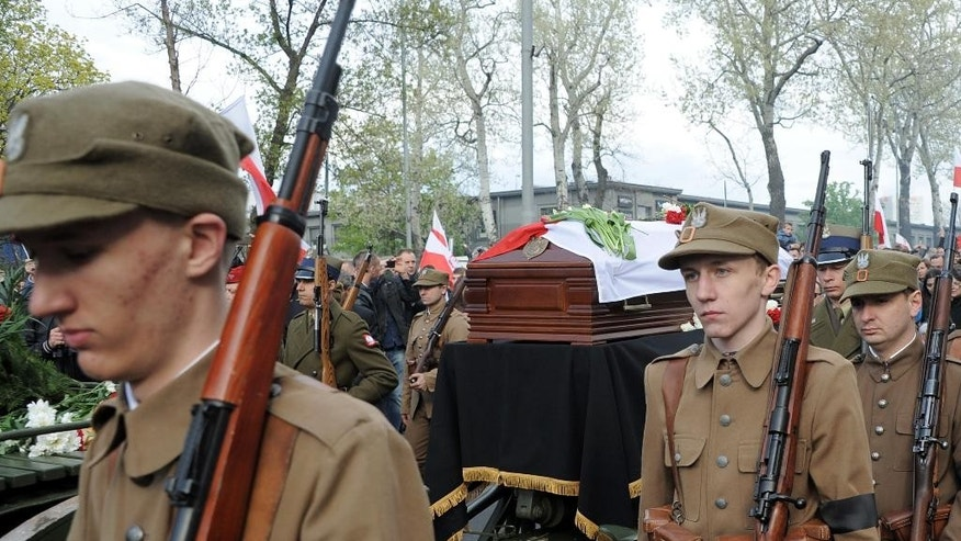 Young men dressed in World War II Polish Army uniforms walk next to the coffin with the remains of Zygmunt Szendzielarz during his funeral in Warsaw, Poland, Sunday, April 24, 2016. Polish President Andrzej Duda and government ministers have taken part in the state burial of Szendzielarz, a World War II resistance commander and communist regime victim whose remains were found in a hidden mass grave. (AP Photo/Alik Keplicz)