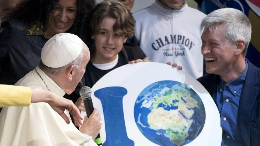 """Pope Francis delivers his speech as he looks at a banner reading """"I Care"""", during his appearance at an Earth Day event in Rome, Sunday, April 24, 2016. Francis made a surprise appearance at the Earth Day event getting up on stage to give an unscheduled address to the delight of the audience in the Villa Borghese park. (Claudio Peri/ANSA via AP) ITALY OUT"""