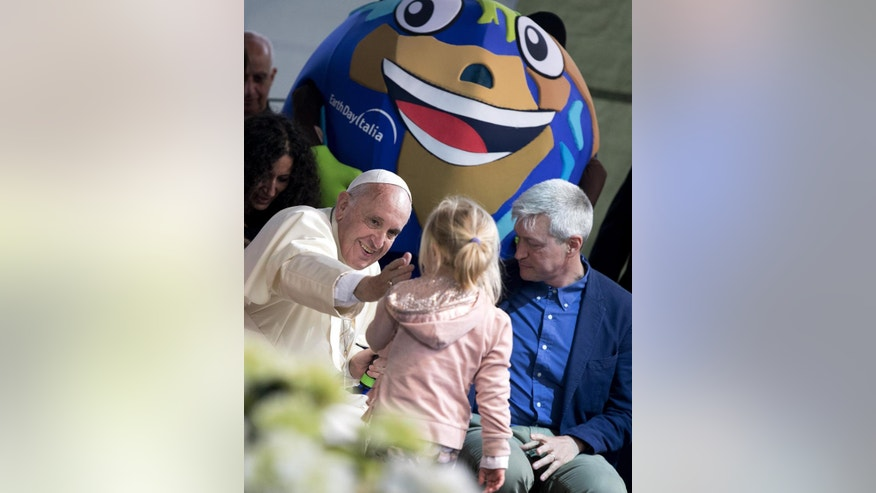 Pope Francis reaches out to caress a young girl during his appearance at an Earth Day event in Rome, Sunday, April 24, 2016. Francis made a surprise appearance at the Earth Day event getting up on stage to give an unscheduled address to the delight of the audience in the Villa Borghese park. (Claudio Peri/ANSA via AP) ITALY OUT