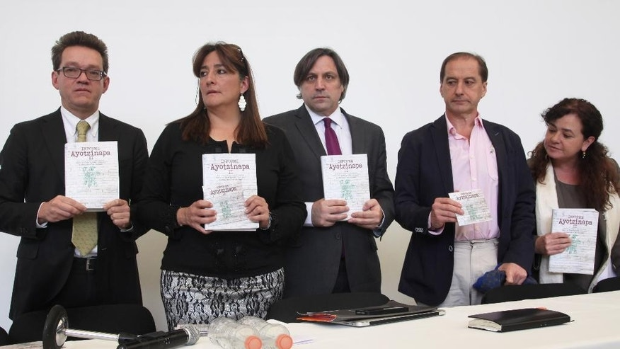 Alejandro Valencia, left, Angela Buitrago, second left, Francisco Cox, center, Carlos Beritain, second right, and Claudia Paz, of the international experts group hold copies of their final report in the disappearance of 43 students, in Mexico City, Sunday, April 24, 2016. The report says there is evidence that Mexican police tortured some of the key suspects arrested in the disappearance of the students. The 43 students have not been heard from since they were taken by local police in September 2014 in the city of Iguala, Guerrero state. (AP Photo/Marco Ugarte)