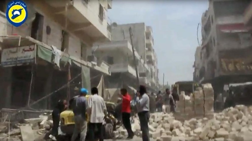 In this image made from video posted online by the Syrian Civil Defense White Helmets, people stand in rubble after airstrikes and shelling hit Aleppo, Syria, Sunday, April 24, 2016. Air strikes and shelling pounded Aleppo for a third straight day Sunday, killing two young siblings and more than a dozen others in Syria's largest city and former commercial capital. (Syrian Civil Defense White Helmets via AP video)