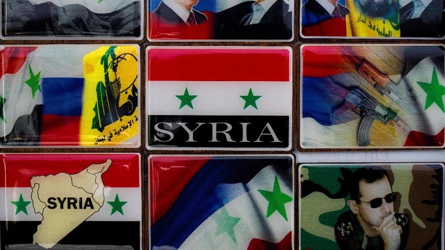 In this Sunday, April 17, 2016 photo, fridge magnets with pictures of Russian President Vladimir Putin, Syrian President Bashar Assad, Hezbollah leader Sheikh Hassan Nasrallah and the Russian, Syrian and Hezbollah national flags are displayed in a souvenirs shop outside the historic 7th century Umayyad Mosque, in Damascus, Syria. Putin, Assad and Nasrallah are a hot commodity in Damascus these days, their faces posted on mementos in the capital's old bazars. (AP Photo/Hassan Ammar)
