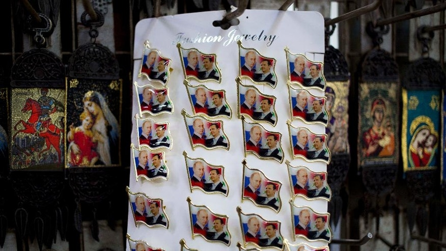 In this Saturday, April 16, 2016 photo, pins with the images of Russian President Vladimir Putin and Syrian President Bashar Assad are displayed in a souvenirs shop outside the historic 7th century Umayyad Mosque, in Damascus, Syria. Putin, Assad and Nasrallah are a hot commodity in Damascus these days, their faces posted on mementos in the capital's old bazars. (AP Photo/Hassan Ammar)