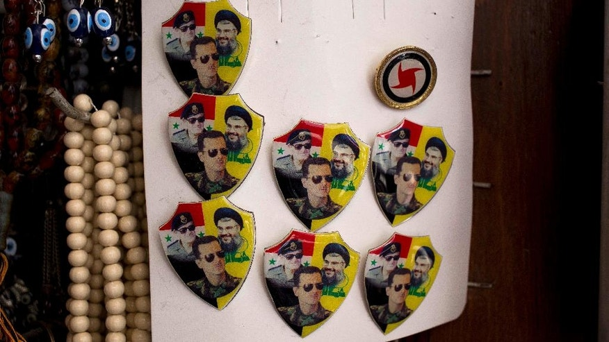 In this Sunday, April 17, 2016 photo, pins with the images of Hezbollah leader Sheikh Hassan Nasrallah and Syrian President Bashar Assad and his father late Syrian President Hafez Assad are displayed in a souvenirs shop outside the historic 7th century Umayyad Mosque, in Damascus, Syria. Putin, Assad and Nasrallah are a hot commodity in Damascus these days, their faces posted on mementos in the capital's old bazars. (AP Photo/Hassan Ammar)