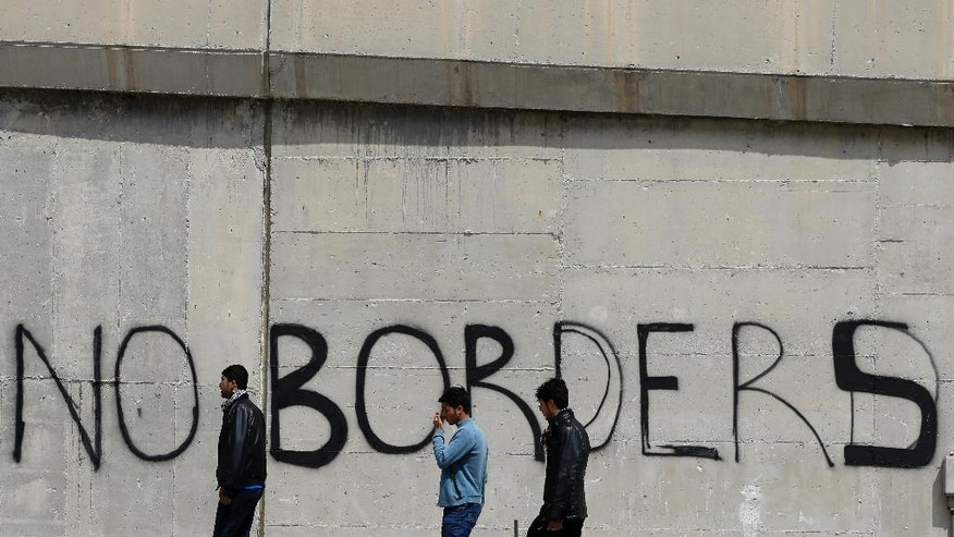 Migrants walk past graffiti at the port city of  Piraeus, Greece on Monday, April 25, 2016. Around 3,500 migrants remain in Piraeus using tents, a warehouse and a terminal passenger building for shelter, as over 50,000 stranded refugees and migrants remain in the country. (AP Photo/Thanassis Stavrakis)