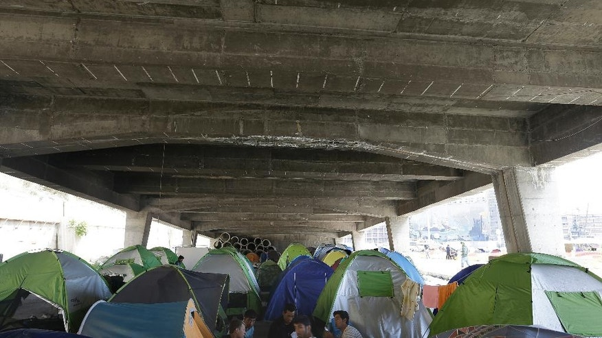 Afghan migrants play cards outside their tents under a bridge at the port city of Piraeus, Greece, on Monday, April 25, 2016. Around 3,500 migrants remain at Piraeus living in tents, a warehouse and a terminal passenger building, as over 50,000 stranded refugees and migrants remain in the country. (AP Photo/Thanassis Stavrakis)