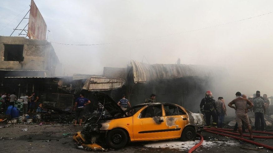 Iraqi firefighters extinguish a fire following a suicide bomb attack in the capital's eastern Shiite-dominated New Baghdad neighborhood, Iraq, Monday, April 25, 2016. A suicide bomber blew up his explosives-laden car Monday in a commercial area in the Iraqi capital, Baghdad, killing and wounding civilians, officials said. (AP Photo/Khalid Mohammed)