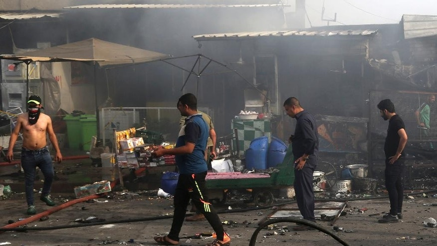Shops owners try to rescue their goods as civilians gather at the scene of a suicide car bomb attack in the capital's eastern Shiite-dominated New Baghdad neighborhood, Iraq, Monday, April 25, 2016. A suicide bomber blew up his explosives-laden car Monday in a commercial area in the Iraqi capital, Baghdad, killing at least 12 civilians, officials said. (AP Photo/Khalid Mohammed)