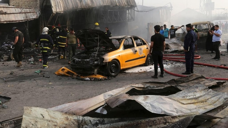 Iraqi firefighters extinguish a fire as civilians gather following a suicide car bomb attack at in the capital's eastern Shiite-dominated New Baghdad neighborhood, Iraq, Monday, April 25, 2016. A suicide bomber blew up his explosives-laden car Monday in a commercial area in the Iraqi capital, Baghdad, killing at least 12 civilians, officials said. (AP Photo/Khalid Mohammed)