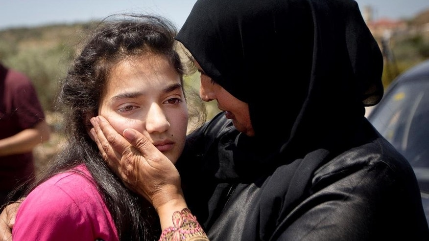 Sabha al-Wawi, right, comforting her daughter, 12-year-old Dima al-Wawi.