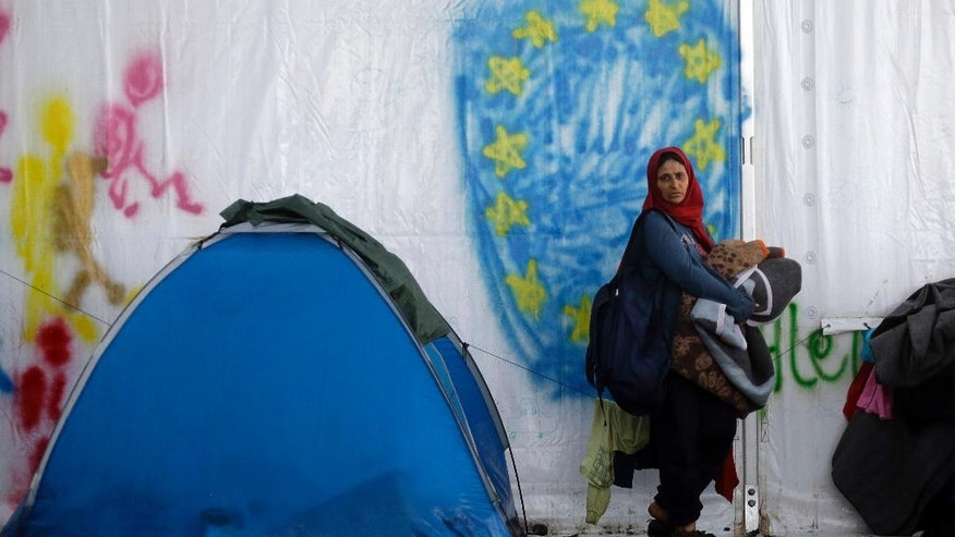 A woman standing in front of a graffiti depicting the EU flag, holds her blankets at the end of a rainstorm at the northern Greek border point of Idomeni, Greece, Sunday, April 24, 2016. Many thousands of migrants remain at the Greek border with Macedonia, hoping that the border crossing will reopen, allowing them to move north into central Europe. (AP Photo/Gregorio Borgia)