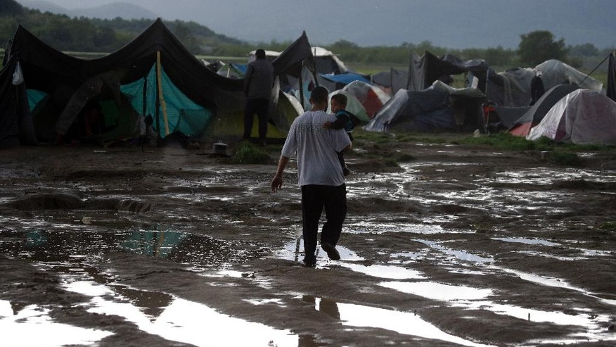 A man holds a child as he walks on a muddy field at the end of a rainstorm at the northern Greek border point of Idomeni, Greece, Sunday, April 24, 2016. Many thousands of migrants remain at the Greek border with Macedonia, hoping that the border crossing will reopen, allowing them to move north into central Europe. (AP Photo/Gregorio Borgia)