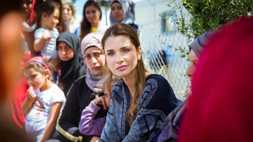 In this picture provided by the Office of Her Majesty Press Department, Queen Rania of Jordan, center, meets with refugees and migrants during her visit to Kara Tepe municipality camp in the Greek island of Lesbos, Monday, April 25, 2016. (Office of Her Majesty Press Department via AP)