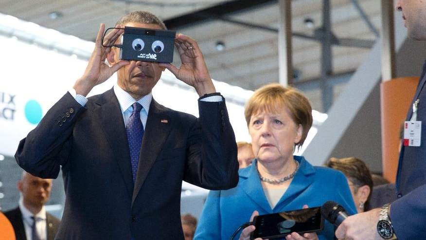 German Chancellor Angela Merkel looks on as U.S President Barack Obama tests VR goggles when touring the Hannover Messe, the world's largest industrial technology trade fair, in Hannover, northern Germany, Monday, April 25, 2016. Obama is on a two-day official visit to Germany. (AP Photo/Carolyn Kaster)