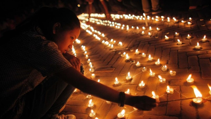 Nepalese people light candles in memory of those who died in last year's devastating earthquake in Basantapur Durbar Square in Kathmandu, Nepal, Sunday, April 24, 2016. Nepalese held memorial services to mark the anniversary of the disaster that killed nearly 9,000 people and left millions homeless. (AP Photo/Niranjan Shrestha)