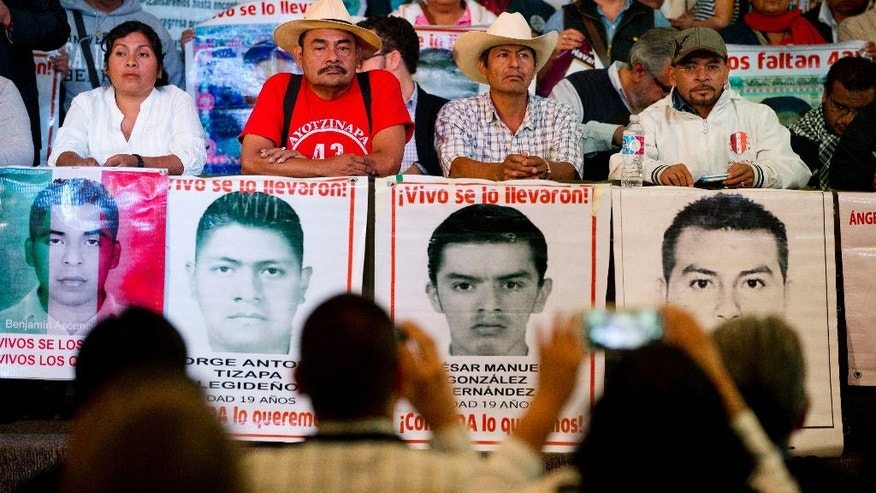 Relatives of 43 missing students, accompanied by their spokesman and human rights activists, take their seats during a press conference to give the families' response to a report issued Sunday by the Inter-American Commission on Human Rights expert group in Mexico City, Monday, April 25, 2016. There is strong evidence that Mexican police tortured some of the key suspects arrested in the disappearance of 43 students, according to the report. The group also complained the government was slow to deliver some of the evidence it had asked for and criticized government prosecutor's investigations as flawed and incomplete. (AP Photo/Rebecca Blackwell)