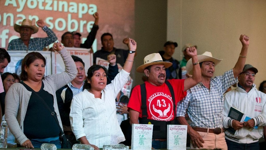 Spokesman Felipe de la Cruz, center, chants along with parents of some of 43 missing students during a press conference to give the families' response to a report issued Sunday by the Inter-American Commission on Human Rights expert group in Mexico City, Monday, April 25, 2016. There is strong evidence that Mexican police tortured some of the key suspects arrested in the disappearance of 43 students, according to the report. The group also complained the government was slow to deliver some of the evidence it had asked for and criticized government prosecutor's investigations as flawed and incomplete. (AP Photo/Rebecca Blackwell)