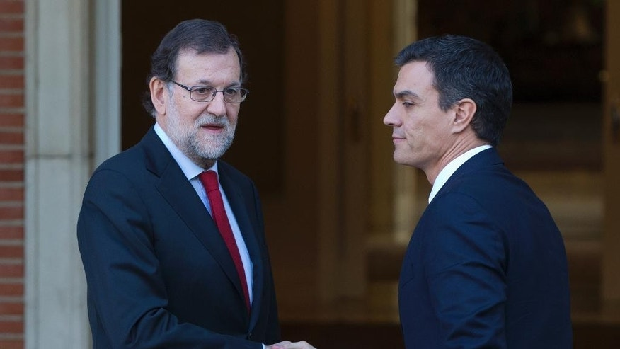 FILE - In this Wednesday, Dec. 23, 2016 file photo, Spain's acting Prime Minister Mariano Rajoy, left, shakes hands with main Socialist opposition leader Pedro Sanchez before a meeting at the Moncloa Palace in Madrid, Spain. Spain's king is meeting Monday, April 25, 2016 and Tuesday with the country's political parties following four months of political paralysis in a last-ditch effort to install a government and avoid sending voters back to the ballot box. The national election last December was historic because it ended the country's traditional two-party system with strong showings for two upstart parties that benefited from voter outrage over soaring unemployment, corruption and austerity cuts. (AP Photo/Paul White, File)